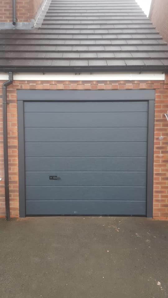 Alutech - M-Ribbed sectional garage door in anthracite grey with a wood grain finish. This door is manually operated via standard locking and 1 standard black handle.