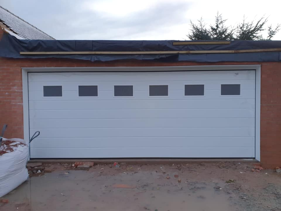 1 x white Alutech sectional garage door in the M-ribbed design with a woodgrain finish. This door also includes 6 windows with plain frosted glass