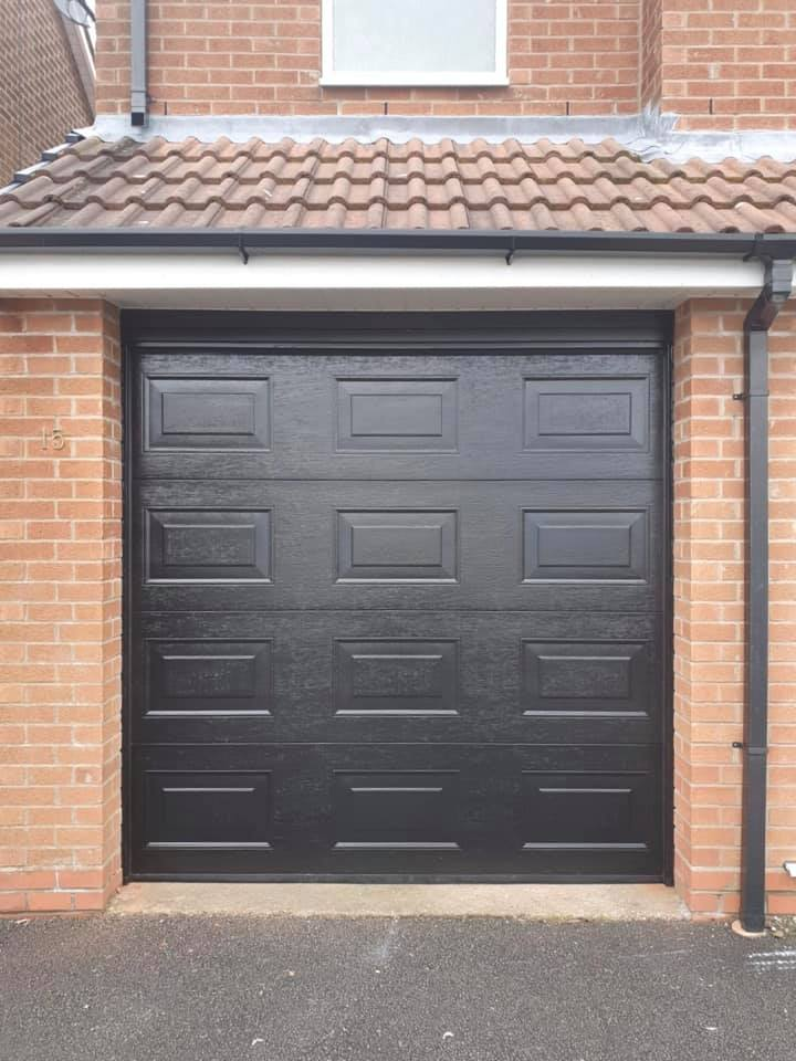 Alutech sectional garage door in the Georgian design finished in black with a woodgrain finish and colour matching tracks.