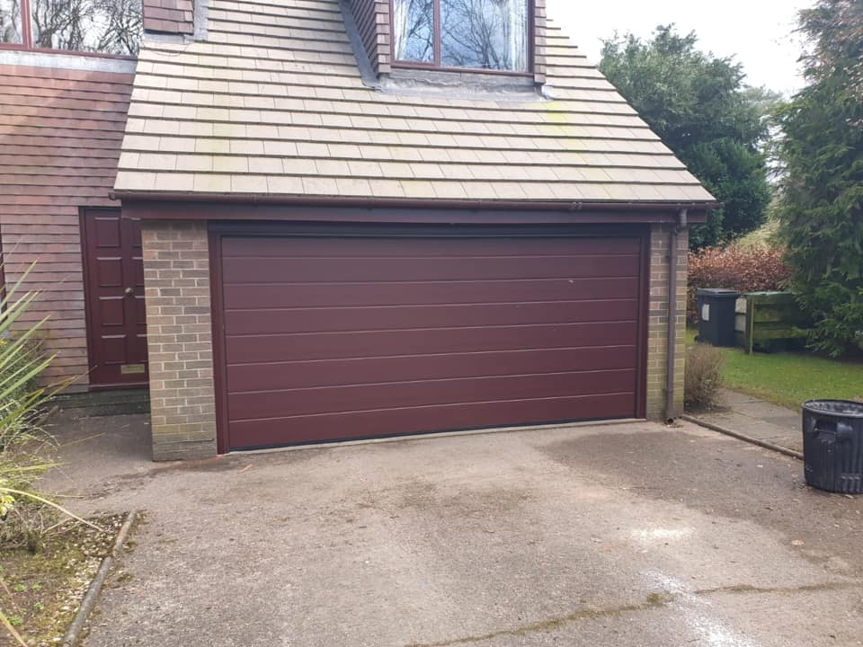Alutech sectional garage door in the M-ribbed design with a rosewood effect and finished with a matching frame.