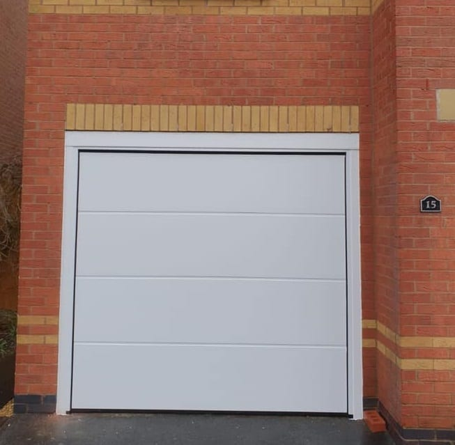 Alutech sectional garage door in the L-ribbed design with a smooth finish, powder coated white.