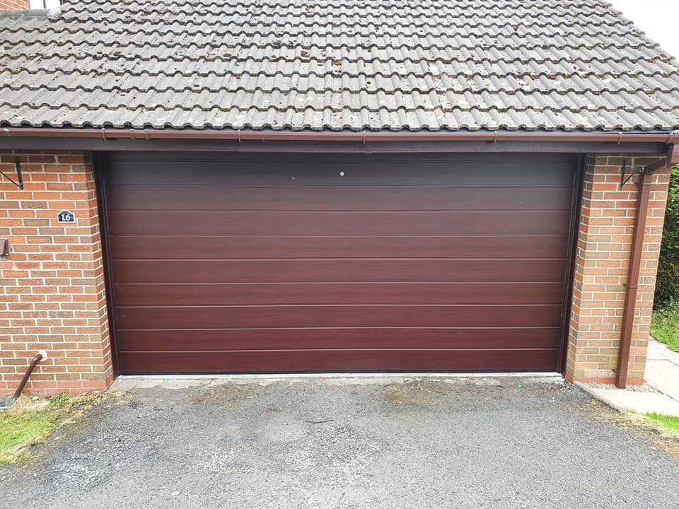 1 x double, Alutech sectional garage door in the M-Ribbed design with the Rosewood effect and a smooth finish. Colour matching tracks have also been added.