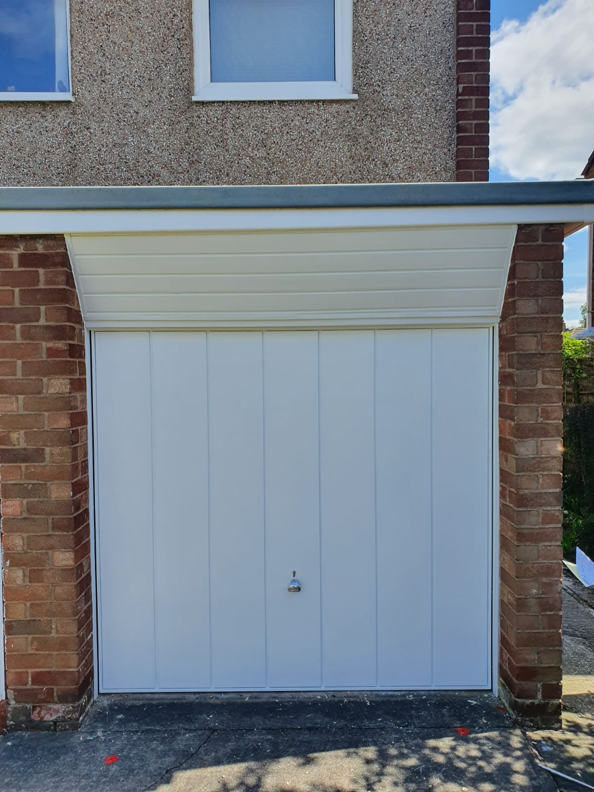 White Garador canopy framed up and over garage door in the Windsor vertical design with a matching frame. Door is manually operated via standard locking with a chrome handle to finish