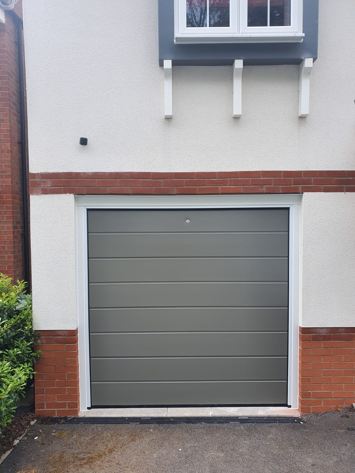 Alutech sectional garage door in the M-ribbed design, RAL 7039 with a smooth finish, complete with white tracks. Door is electrically operated and complete with 1 x sectional door motor, external release kit and 2 x remote handsets.