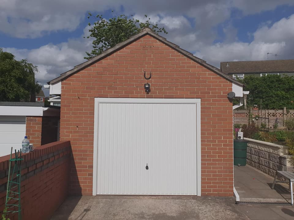 Canopy framed up and over garage door in the standard vertical design, powder coated white with a matching frame.