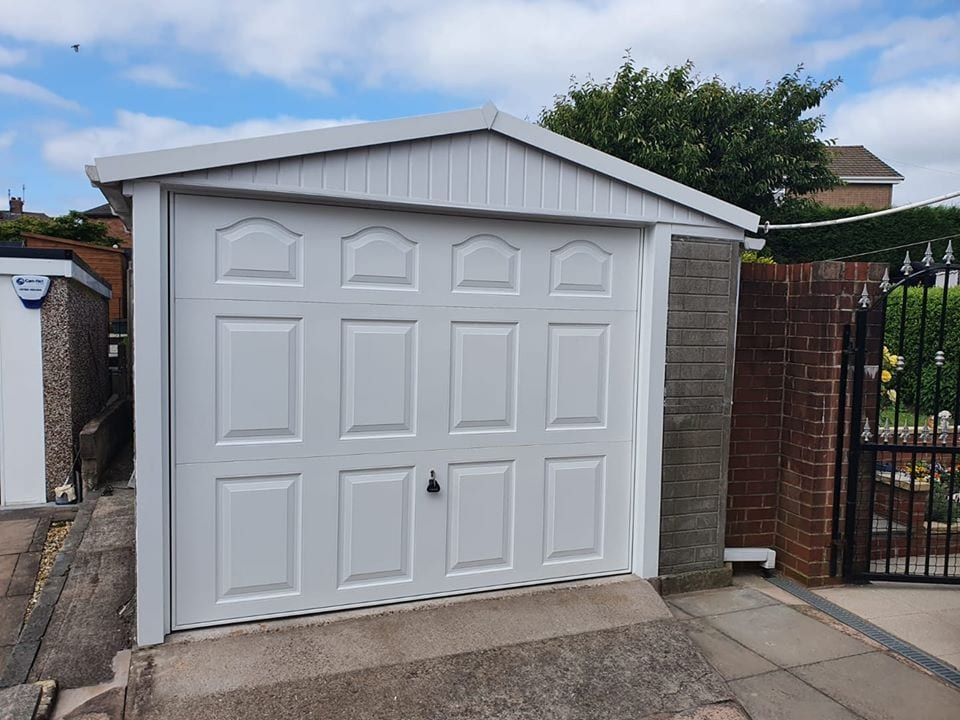 Garador - Manually operated, retractable framed up and over garage door in the Cathedral design, powder coated white with a matching frame.