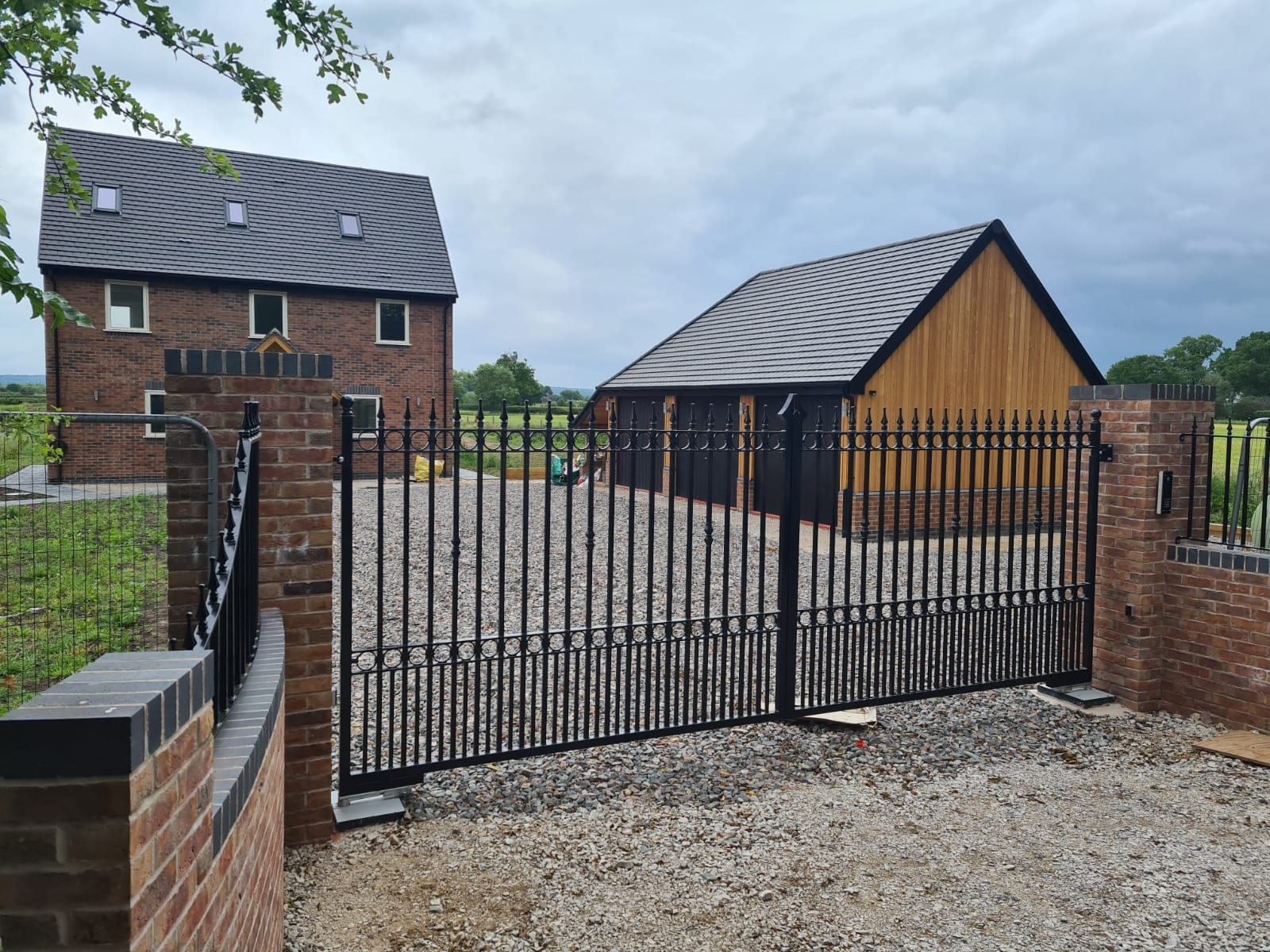A pair of automated wrought iron swing gates, galvanised and powder coated black to finish with a set of railings to mach